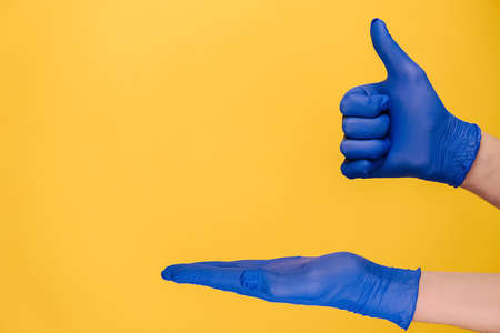 Unrecognizable young male opening palm and makes thumb up gesture, demonstrates approval or agreement, wears medical protective gloves, isolated on yellow wall for advertisement. Body language concept