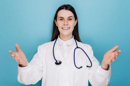Happy young woman doctor at clinic or hospital welcoming patient, telling good news after treating person from covid 19 severe symptoms, gesturing and smiling, wear white coat, isolated on blue wall