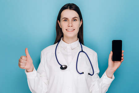 Professional female doctor showing smartphone screen and smiling, demonstrate thumb-up gesture and internet appointment app, isolated on blue background. Healthcare workers and online medicine concept