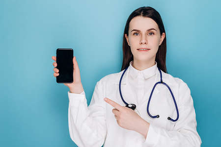 Pozitive young female doctor pointing finger at mobile screen, recommend download checkup, consultation application, isolated on blue wall. Covid-19, healthcare workers and online medicine concept Stok Fotoğraf