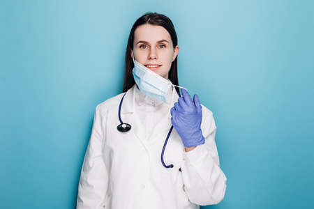 Professional female doctor in latex protective gloves removing face mask, wears white uniform and stethoscope, isolated on blue background. Covid 19, healthcare workers and preventing virus concept