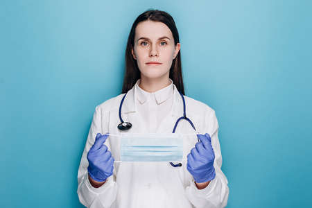 Portrait of professional young woman doctor or nurse in latex gloves holding medical protective face mask, looking at camera, dressed white coat and stethoscope, isolated on blue studio background.