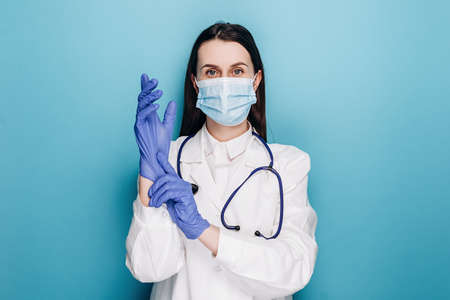 Professional young female physician, doctor in medical mask and white coat, put on rubber gloves for examination, isolated on blue background. Covid-19, coronavirus disease, healthcare workers concept Stok Fotoğraf