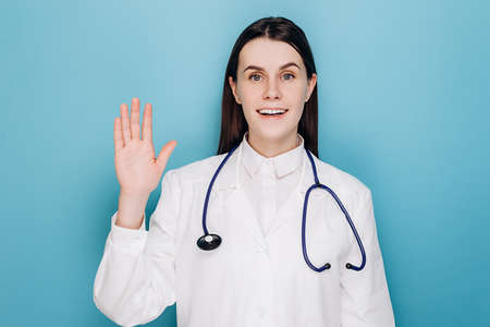 Beautiful friendly young doctor woman wearing medical uniform waving saying hello happy and smiling, welcome gesture, isolated on blue studio background. Covid 19, virus, health and medicine concept