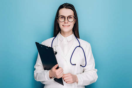 Portrait of cheerful professional young female doctor or nurse in eyeglasses and white uniform holding clipboard, happy looking at camera, isolated on blue studio background. Medical workers concept
