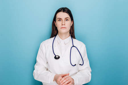 Anxious young woman doctor feels mental burnout at work, looking unhappy at camera, wears coat, stethoscope, isolated on blue background. Stressed frustrated physician upset about medical failure