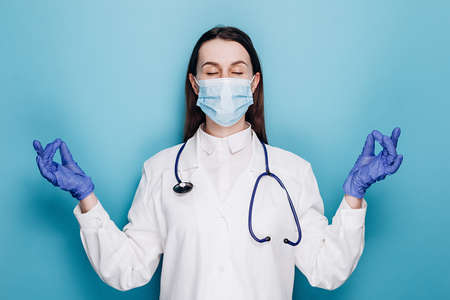 Calm woman doctor, nurse in uniform staying relaxed, meditating with eyes closed and happy smile, wears medical mask and gloves, isolated on blue wall. Healthcare workers and preventing virus concept Stok Fotoğraf