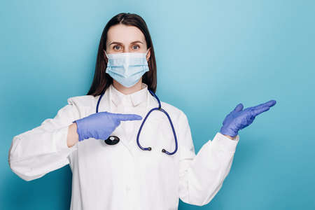 Pleasant caucasian female doctor, medical employee in white coat and face mask, pointing fingers upper right corner, showing advertisement. Covid-19, coronavirus disease, healthcare workers concept Stok Fotoğraf