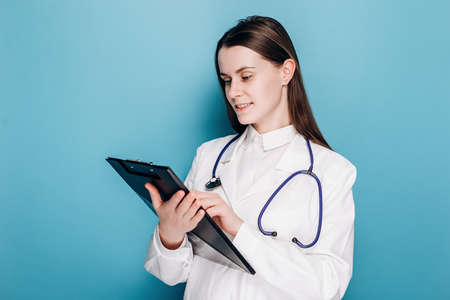 Portrait of cute professional young woman physician specialist in white coat standing on blue studio background with copy space, writing down symptoms. Healthcare workers and vaccination concept Stok Fotoğraf