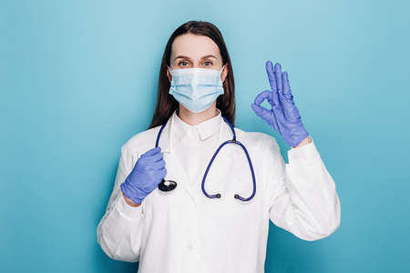 Young woman doctor in medical mask and white coat, rubber gloves, ensure everything alright, show okay gesture, isolated on blue studio background. Social distancing and coronavirus pandemic concept