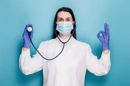 Portrait of millennial woman doctor or nurse in medical protective mask and gloves with stethoscope in ear listen you carefully attentively, demonstrate ok sign, isolated on blue studio background
