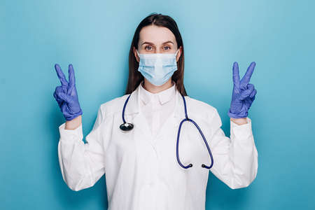 Optimistic cute woman doctor ask to stay safe, wear medical mask and latex gloves, show peace sign, hope we defeat virus pandemia, isolated on blue wall. Covid 19, healthcare and doctors concept