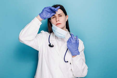 Young doctor woman or nurse in gloves and mask suffering from headache desperate and stressed because pain and migraine, wears stethoscope and white coat, isolated over blue background. Hand on head