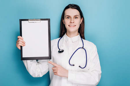Professional cute woman doctor pointing at clipboard paper, explain disease or showing chart, wear white coat and stethoscope. Covid 19, preventing virus, healthcare workers and vaccination concept Stok Fotoğraf