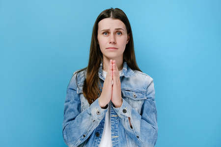 Portrait of pleading young woman hold hands folded prayer gesture begging about something say please, dressed in denim jacket, posing isolated on blue studio background wall. Wealth and hope concept