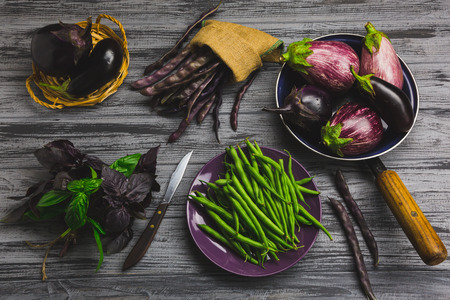 Raw organic vegetables on a gray wooden board. Top view Imagens - 91827964