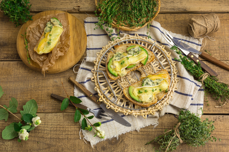 Healthy sandwiches with avocado, cheese and herbs. On wooden background, top view.