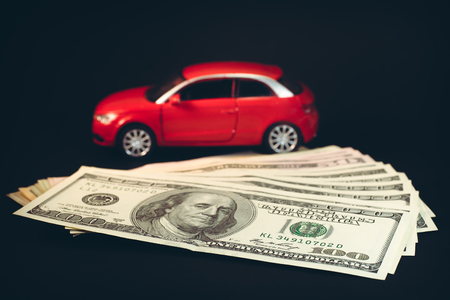 Car on a background of dollars on a black background. Red car on a background of dollars. Big dollar banknotes on a black background.