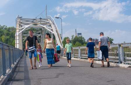 dnepr: Dnepropetrovsk, Ukraine - August 15, 2015: Group of people walking through pedestrian bridge from central park to Komsomolsky island on a Dnepr river