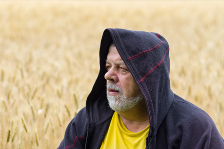 cowl: Outdoor portrait of a senior man in cowl against wheat field