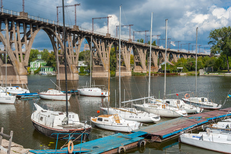 anchorage: Dnepropetrovsk, Ukraine - September 29, 2013: Yacht-club anchorage at arched bridge at fall season