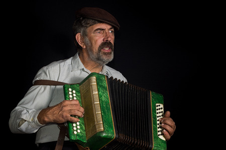 Portrait low key of an old Ukrainian peasant singing while playing button accordion Фото со стока