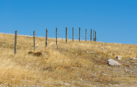 guarded: Guarded landscape - barrier with barbed wire against blue cloudless sky