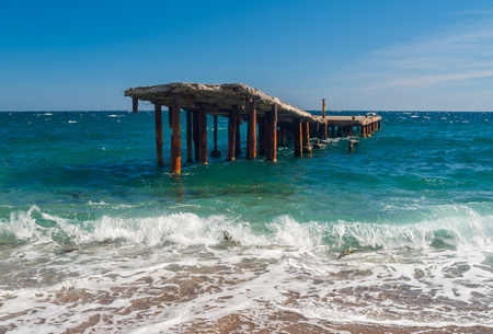 ruinous: Old ruinous pier on a Black Sea shore in Crimea Stock Photo