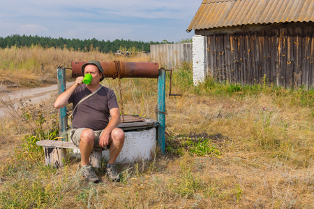 blinders: Tired traveller drinking water at country draw-well in central Ukraine