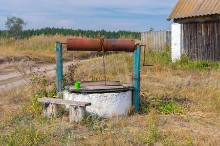 Old country draw-well with wooden bench at in central Ukraine
