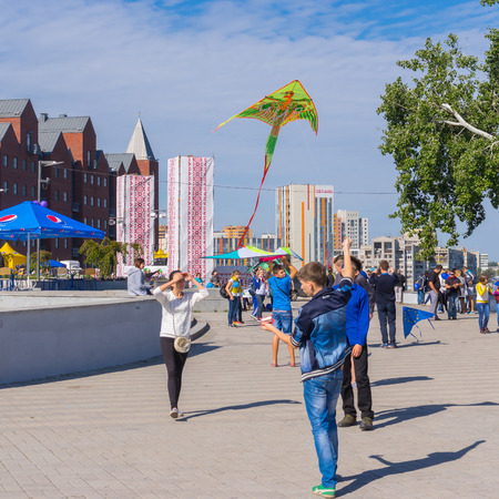 flying kites: DNEPROPETROVSK, UKRAINE - SEPTEMBER 12, 2015: Young people flying kites during City Day local activity, September 12, 2015, Dnepropetrovsk, Ukraine Editorial