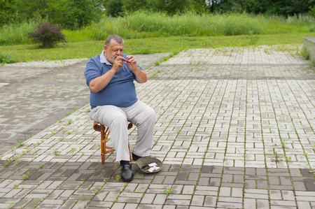 woodwind: Lonely musician on a street playing Ukrainian woodwind instrument sopilka