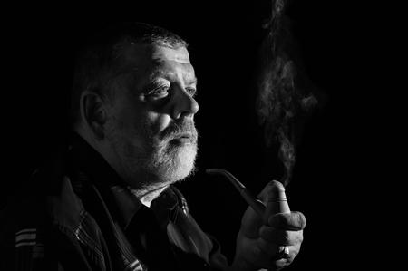 Black and white dramatic portrait of senior smoking tobacco pipe