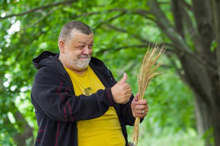 musing: Portrait of a senior farmer showing good harvest Stock Photo