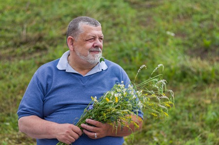 wistful: Outdoor portrait of a happy senior man waiting for the wife with bouquet of wild flowers