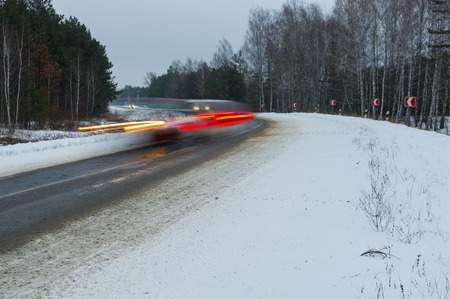 driving conditions: Motion blur of a speedy cars on winter road turn