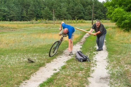 punishing: Senior man punishing bicycle thief with club in Ukrainian rural area