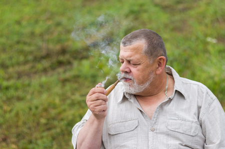 senior smoking: Outdoor portrait of a senior man smoking tobacco-pipe