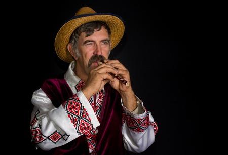 hombre con sombrero: Portrait of Ukrainian farmer with sopilka playing traditional melody