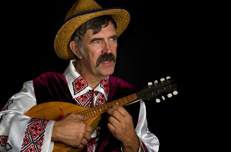 mandolin: Portrait low key of Ukrainian farmer playing mandolin and singing