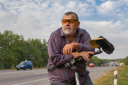 hombre solitario: Retrato al aire libre de un hombre mayor con barba con la bicicleta