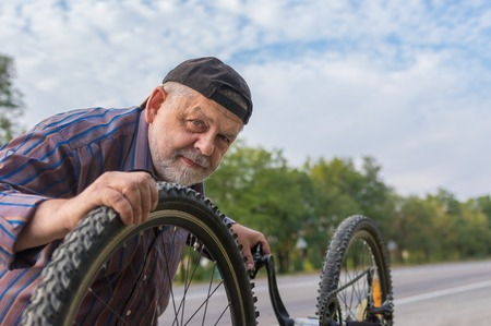 experienced operator: Outdoor portrait of senior bicycle mechanic at work Stock Photo