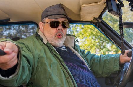 lunacy: Portrait of senior driver making popular selfie in a shabby car
