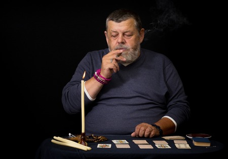 adivino: Retrato de un anciano fumando cigarro antes de la cartomancia Foto de archivo