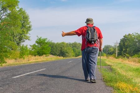 roadside stand: Senior hitchhiker walking on a roadside in Ukrainian rural area at summer time