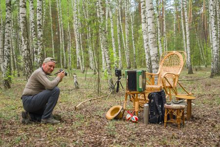 concertina: Portrait of mature photographer on an outdoor photo session