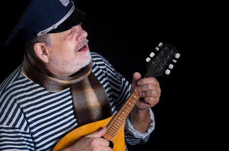 striped vest: Senior man in striped vest and comforter with mandolin playing and singing music