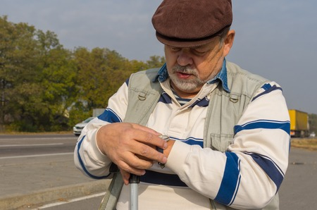 verifying: Outdoor portrait of senior man verifying time with wristwatch