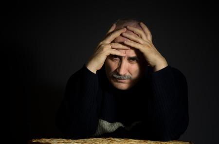 despondent: Portrait of sad mature man with arms enfolded head