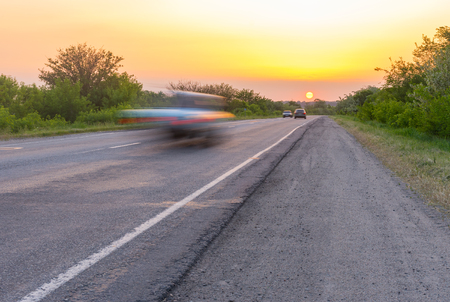 driving conditions: Sunset over rural road with speedy cars racing to the sun